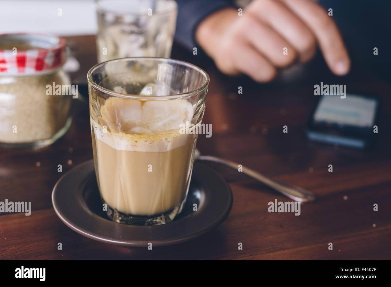 ein Mann mit seinem Handy in einem café Stockbild