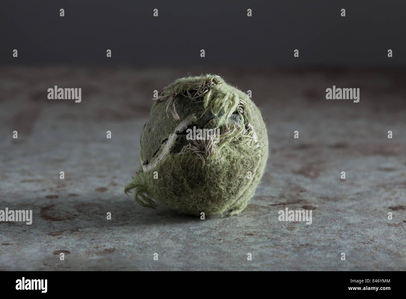 Gebrochene Tennisball auf Grunge-Oberfläche Stockbild