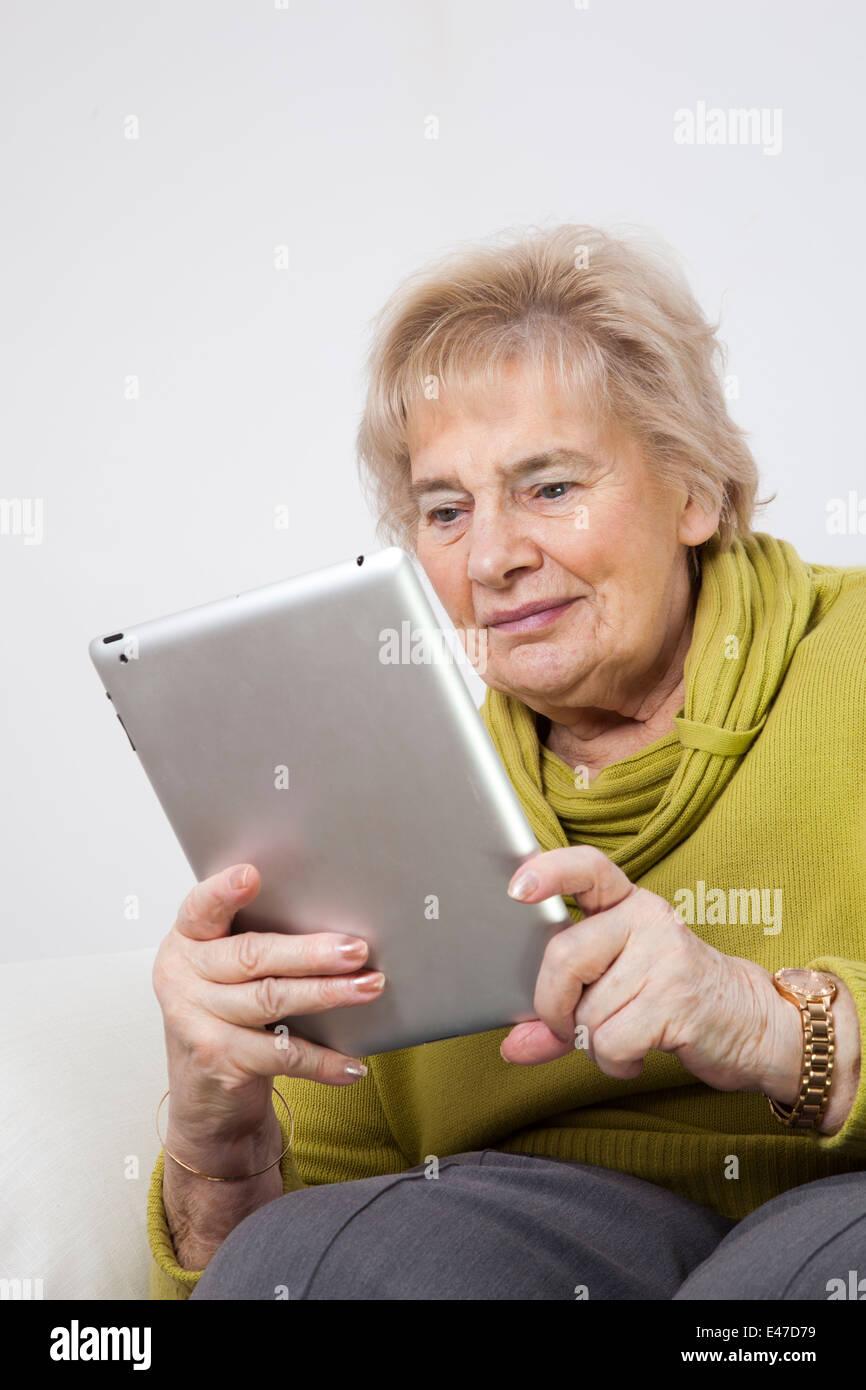Ältere Dame auf der Suche mit einem digitalen Tablet (No-Name i-Pad) Stockbild