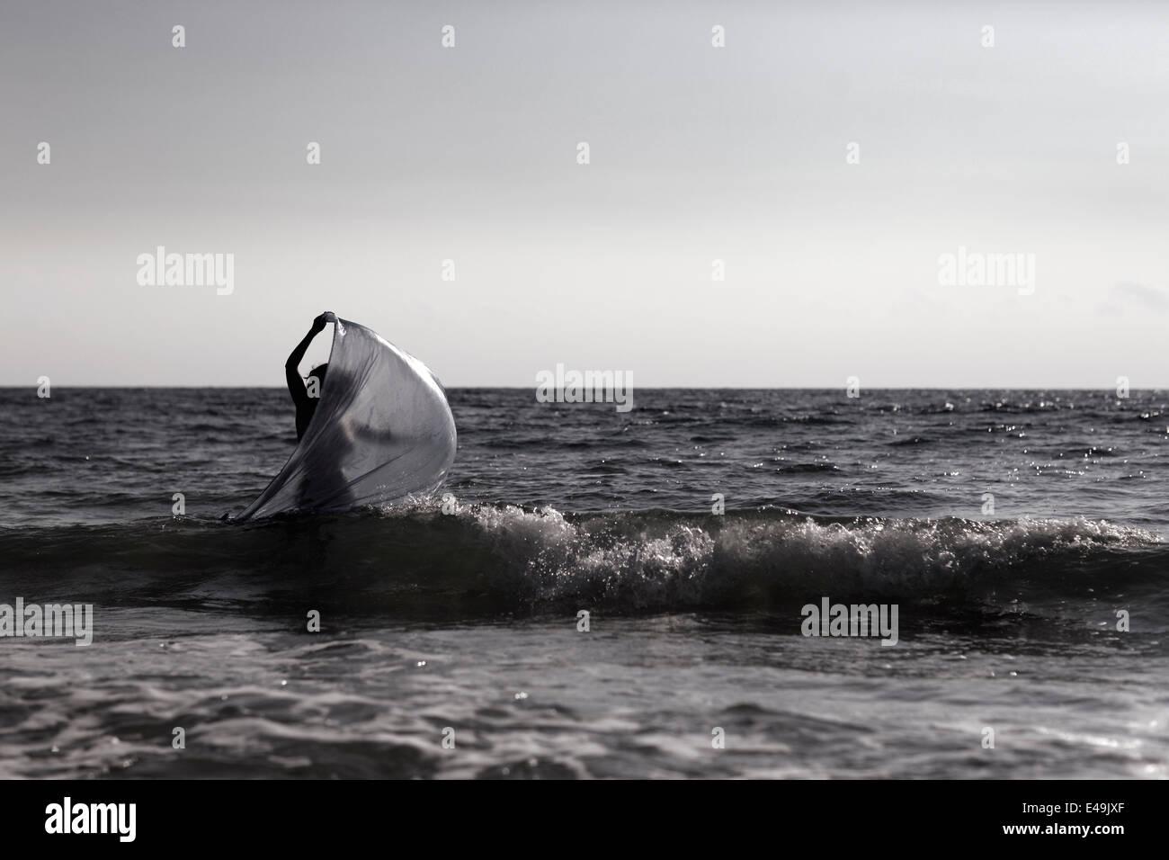 Silhouette der jungen Frau zu Fuß am Meer mit Tuch Stockbild