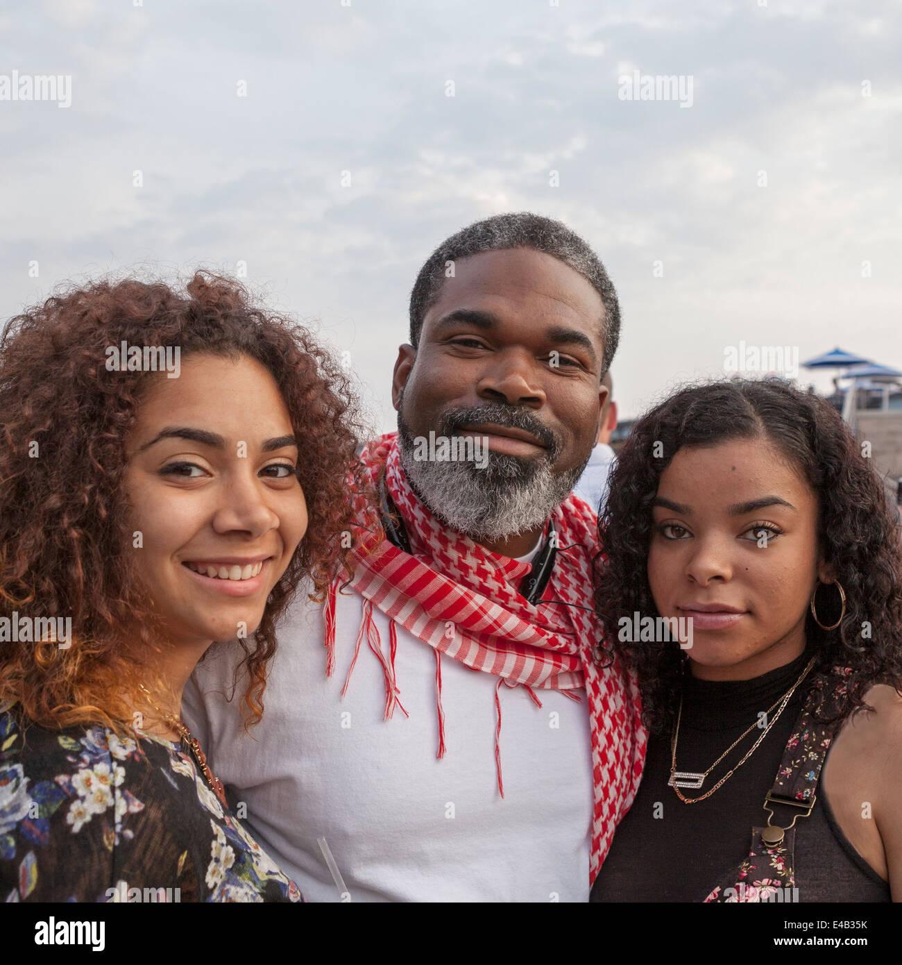 Ein Vater steht mit seinen beiden Töchtern beim Sommerfest, ein jährliches Musikfestival in Milwaukee, Wisconsin Stockfoto