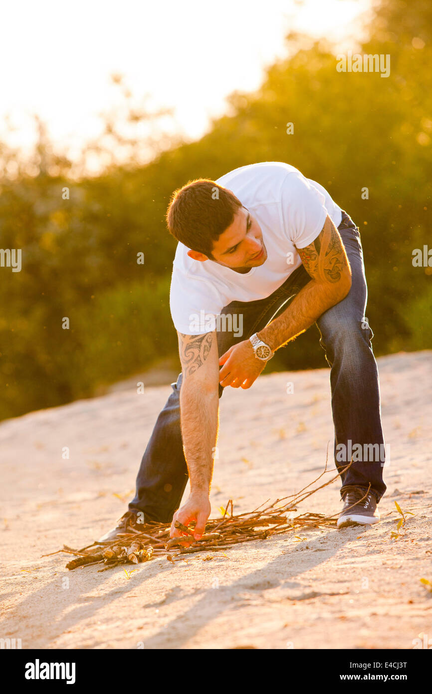 Junger Mann am Ufer sammeln von Brennholz, Osijek, Kroatien Stockbild