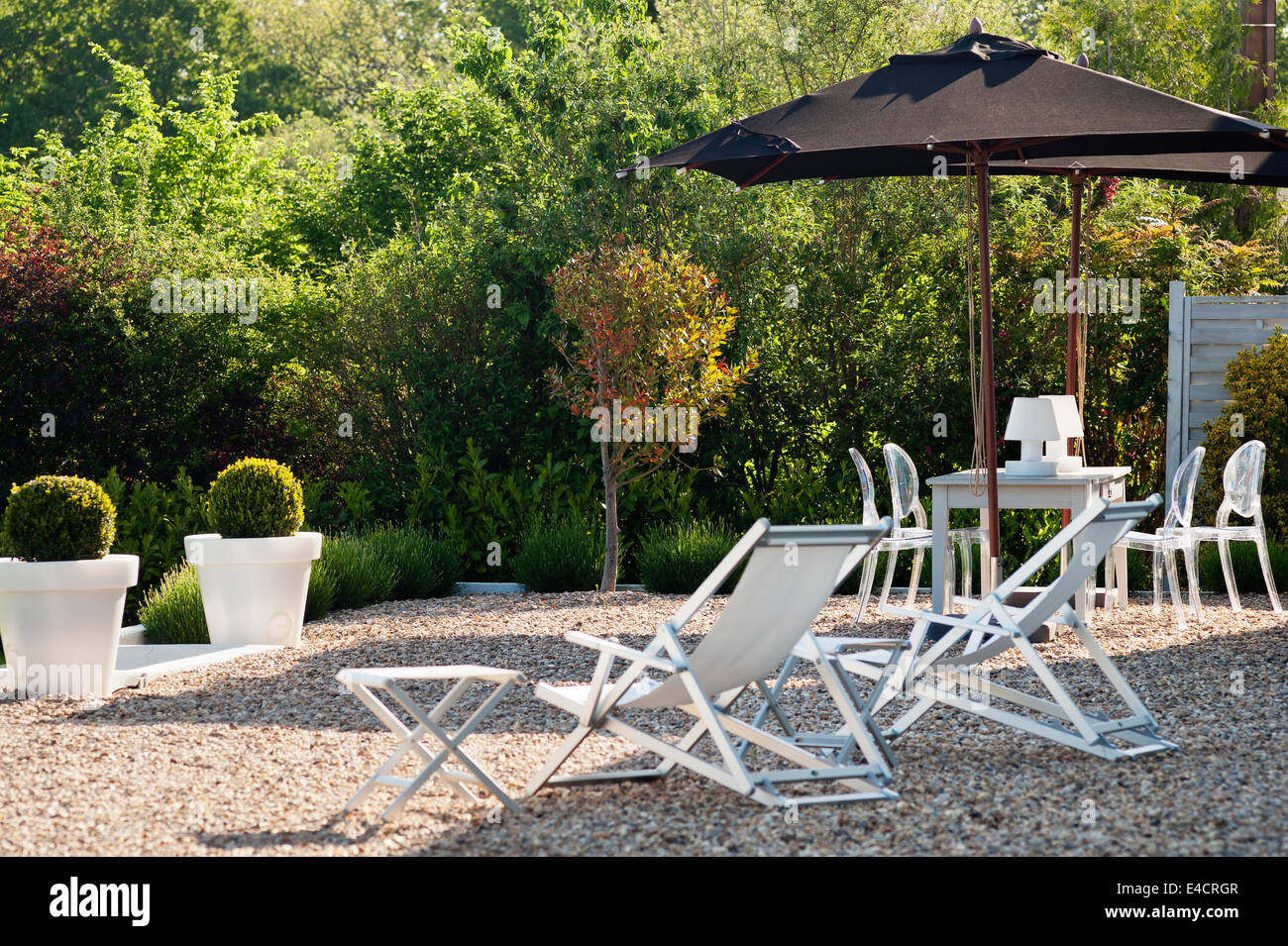 liegestühle und sonnenschirme auf kies terrasse stockfoto, bild