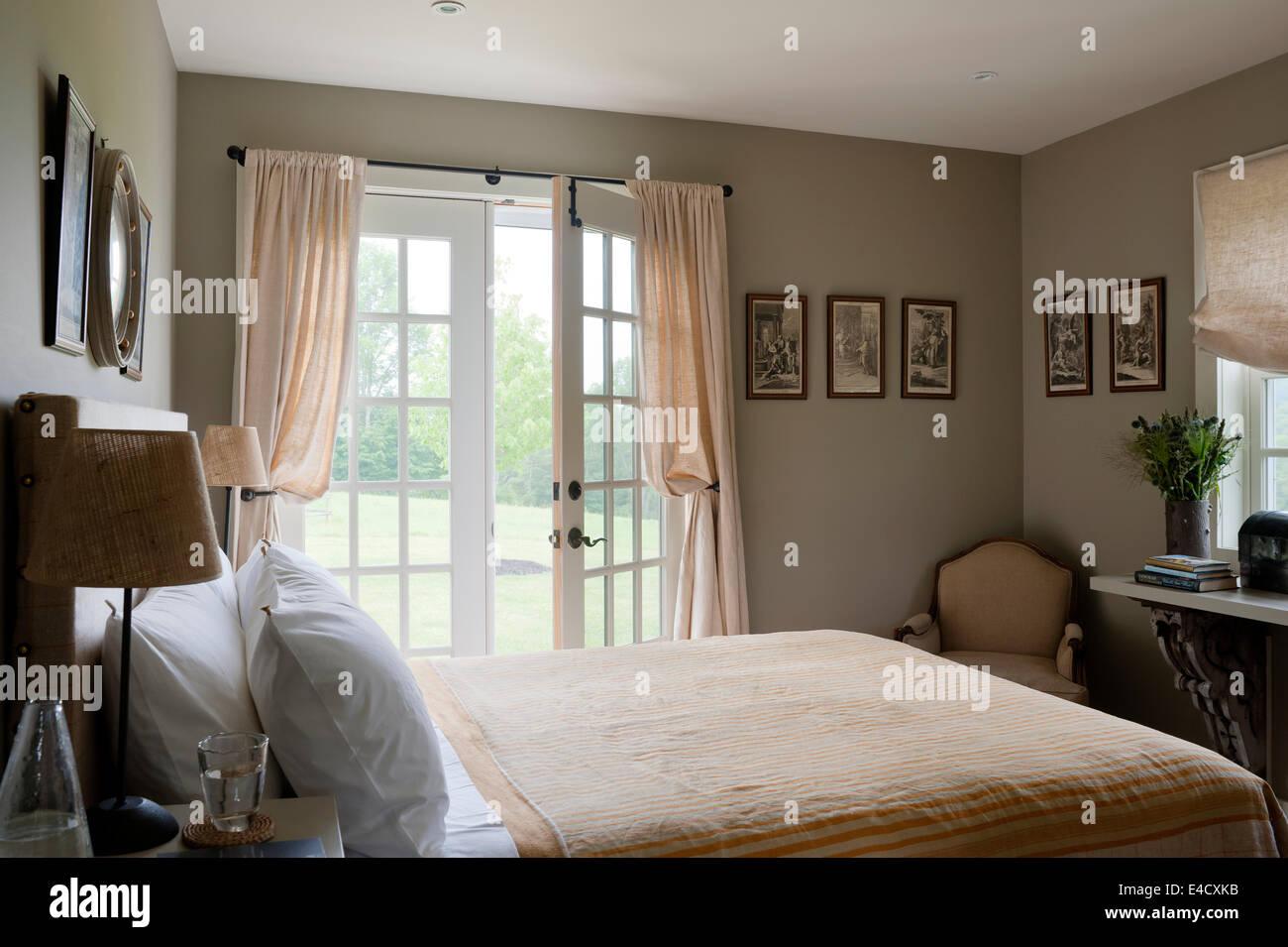 Gestreifte Pfirsich Und Weißer Bettwäsche Im Schlafzimmer Mit Französischen  Fenstern Stockbild