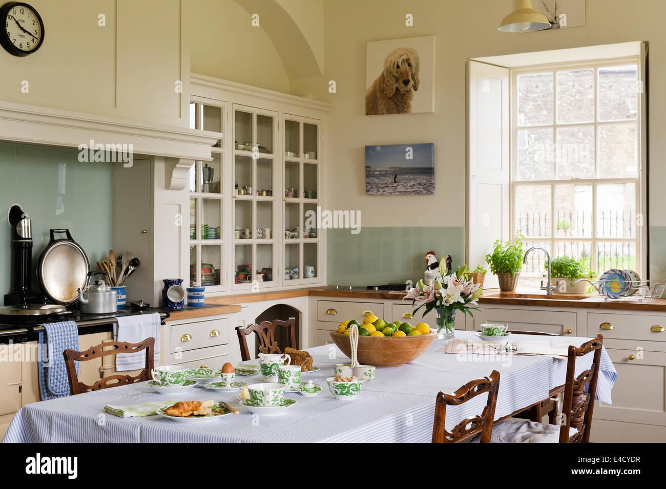 Mouseman Stühle von Thompson von Kilburn und rund um einen Esstisch in einer Landhausküche. Stockbild