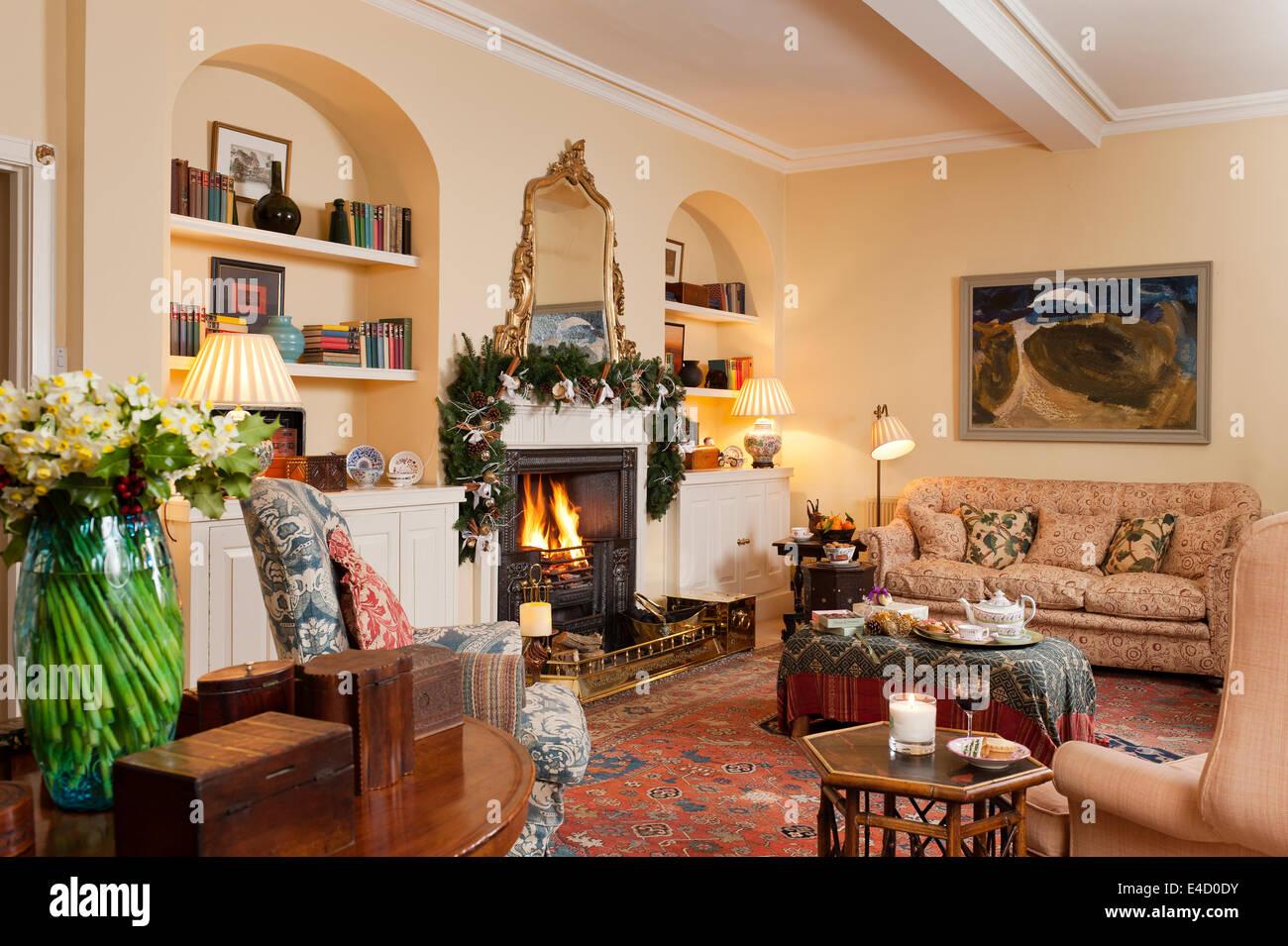 Gemütliches Wohnzimmer mit Kamin und verschiedene antike Möbel. Das ...