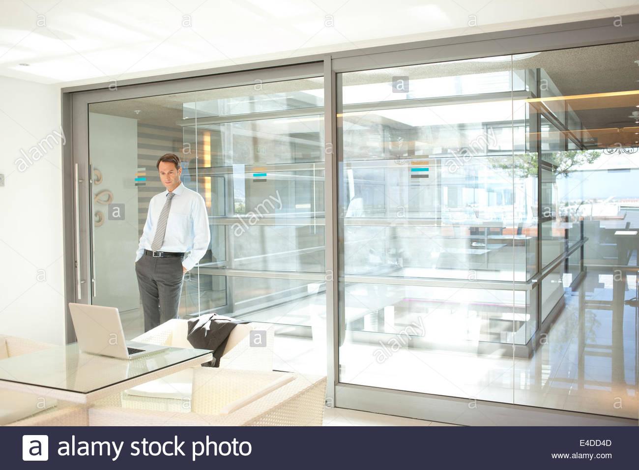 Geschäftsmann gelehnt Glaswand im Büro Stockfoto