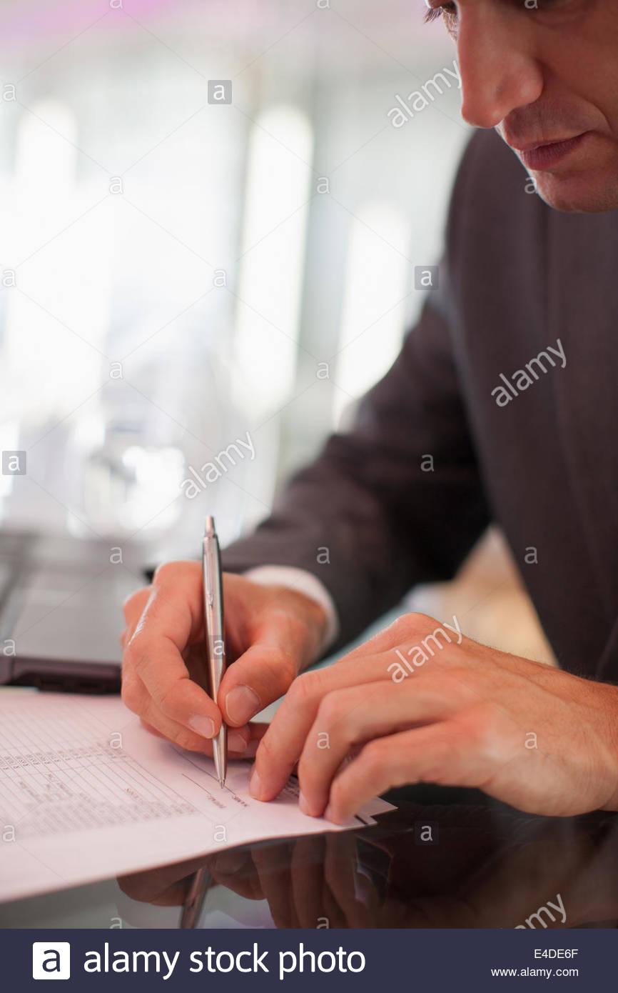 Geschäftsmann, schreiben auf dem Papier am Schreibtisch Stockbild