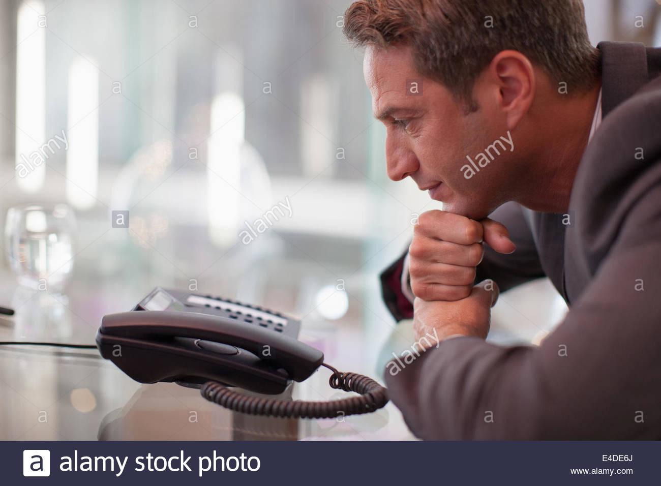 Geschäftsmann starrte Telefon warten, bis es klingelt Stockbild