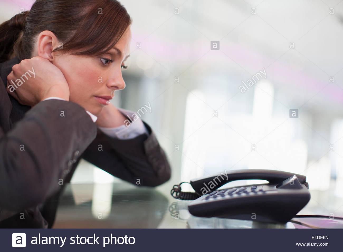 Geschäftsfrau starrte Telefon warten, bis es klingelt Stockbild