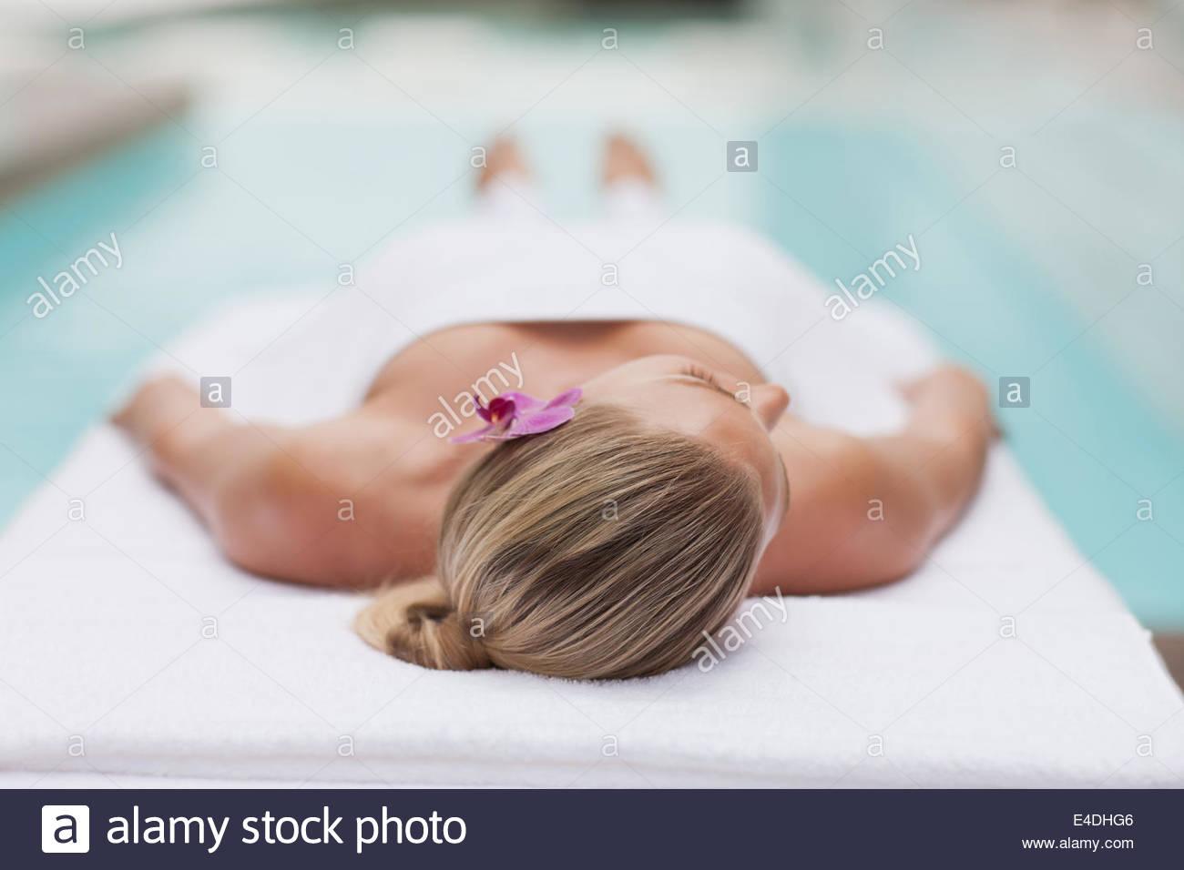 Frau auf Massagetisch am Pool Stockfoto