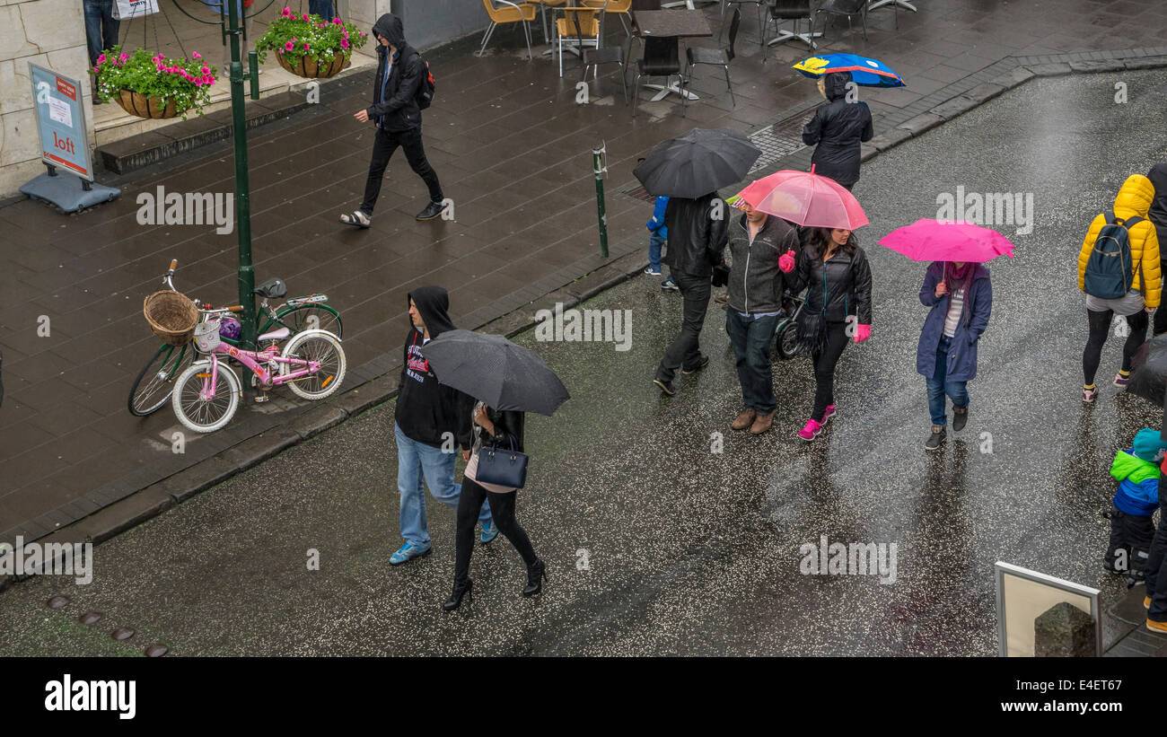 Menschen zu Fuß mit Sonnenschirmen während eines regnerischen Feier. 17. Juni - Tag der Unabhängigkeit Stockbild