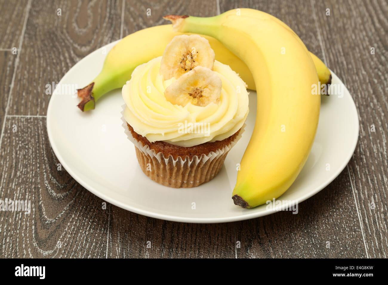 Ein Banane Cupcake mit Buttercreme Zuckerguss garniert und serviert mit frischen Bananen, Studio gedreht Stockbild