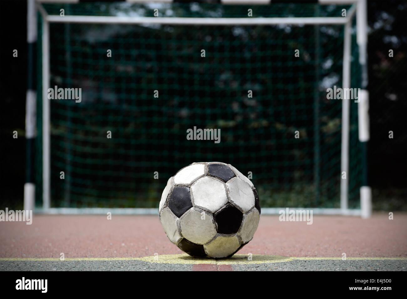 Alte und gebrauchte Fußball auf einer Zement-Spielfeld Stockbild
