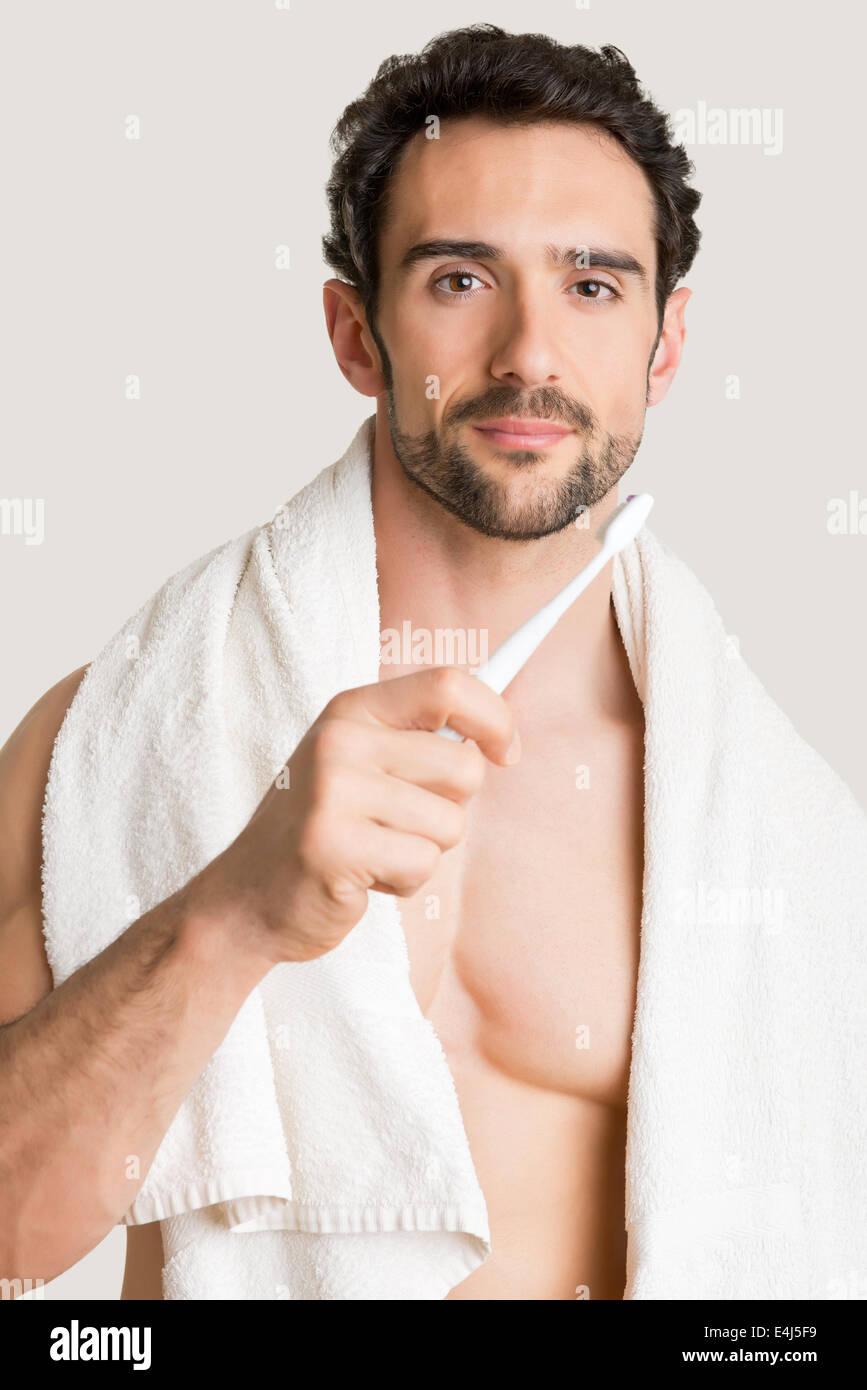 Nahaufnahme des Mannes mit einer Zahnbürste auf seine Hände, seine Zähne zu putzen Stockbild