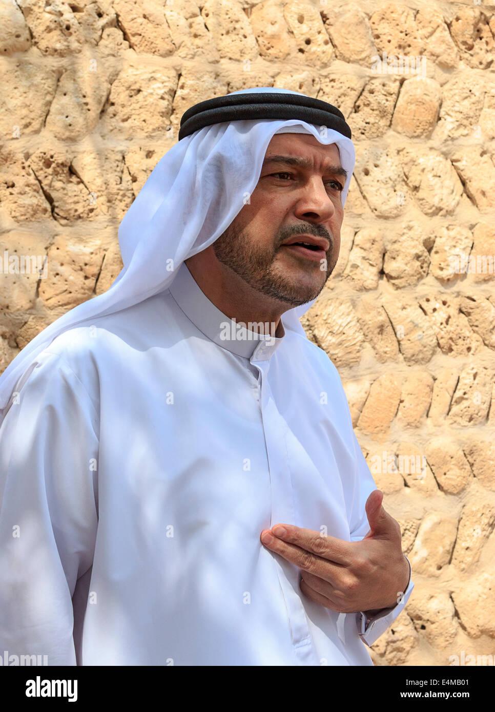 Kayed Nasif, führt in einem traditionellen arabischen Gewand und Kopfschmuck, den Menschen durch Dubai Kulturzentrum Stockbild