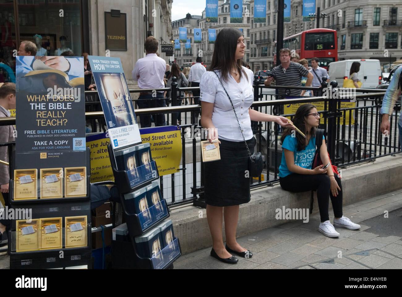 Wach und was tut die Bibel wirklich Lehren Jehovas Zeugen Literatur wird in Oxford Street London HOMER SYKES ausgehändigt Stockbild