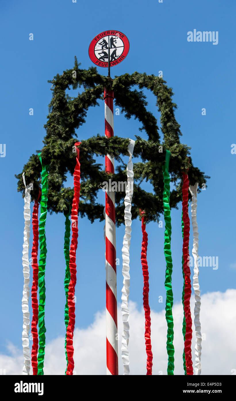 Maibaum, errichtet von der örtlichen Freiwilligen Feuerwehr, Stockbild