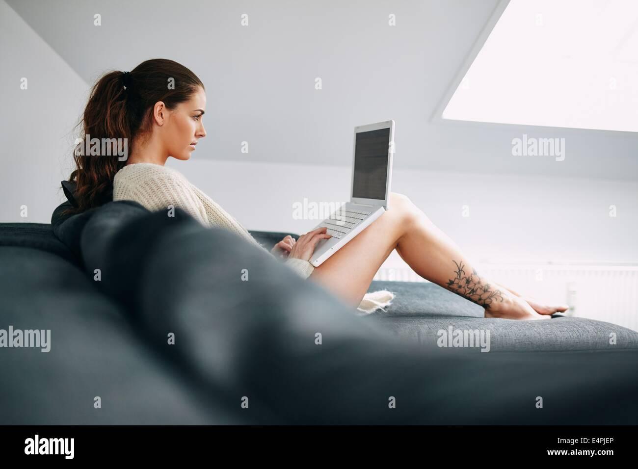 Bild der hübsche junge Brünette mit Laptop zu Hause. Junge Frau sitzend auf Sofa am Laptop arbeiten. Stockbild