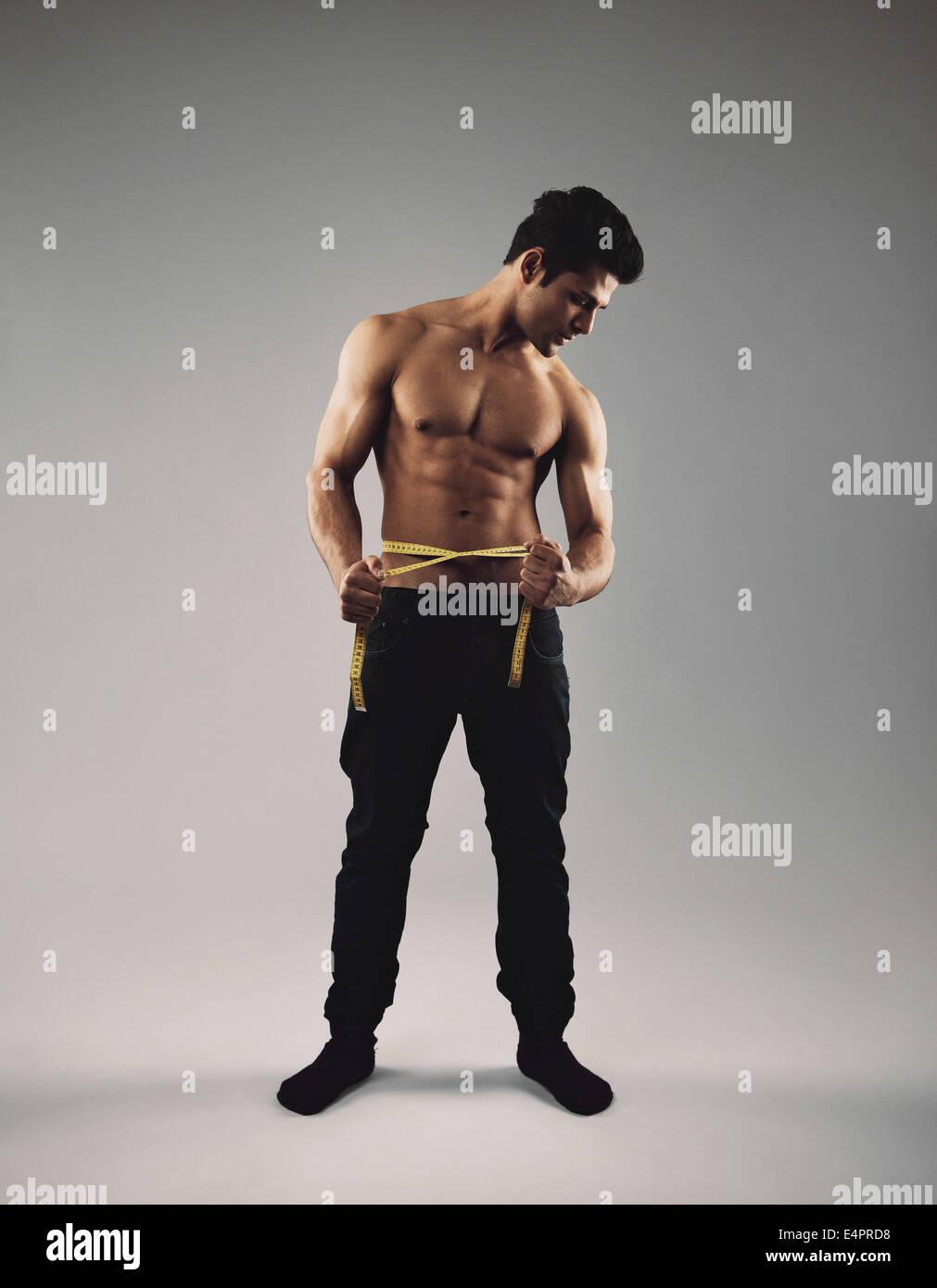 Voller Länge Bild Fit jungen Mannes mit Maßband um seine Taille messen seines Körpers. Maskuline Stockbild