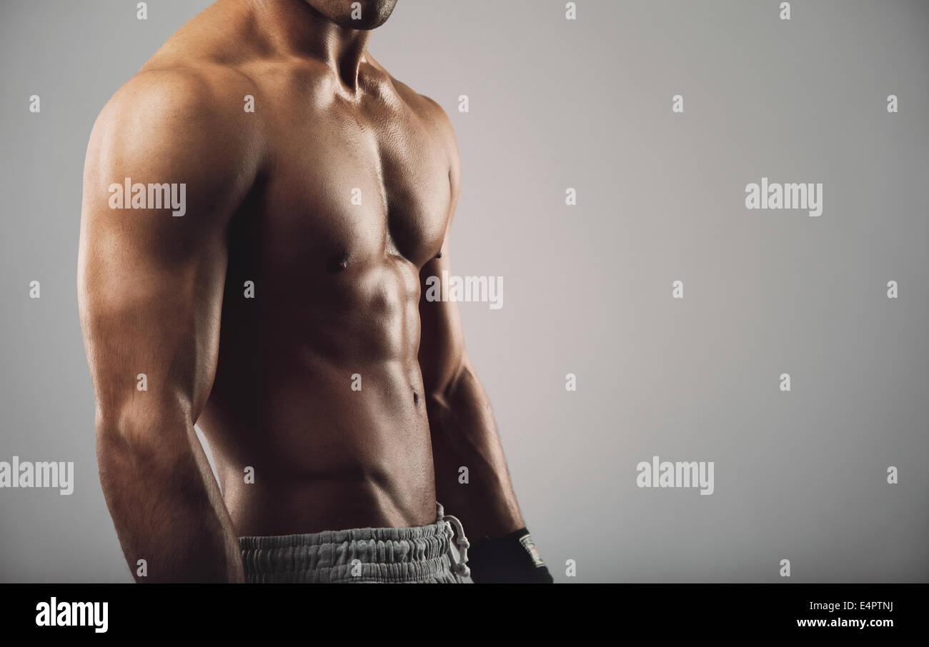 Porträt von nacktem Oberkörper junger Mann stehend auf grauem Hintergrund hautnah. Mann mit muskulösen Stockbild
