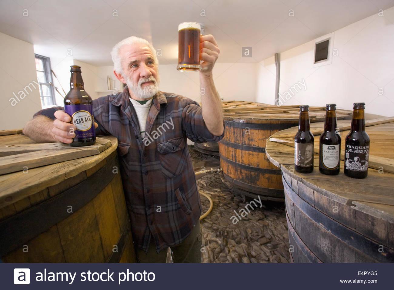 Ein Brauer prüft die Qualität des fertigen Produktes Tun im original Sudhaus in Traquair House Brewery, Stockbild