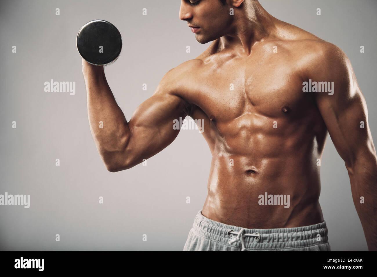 Zugeschnittenes Bild von jungen muskulösen Mann schwere Hantel Übung für Bizeps. Mann mit Hanteln Stockbild