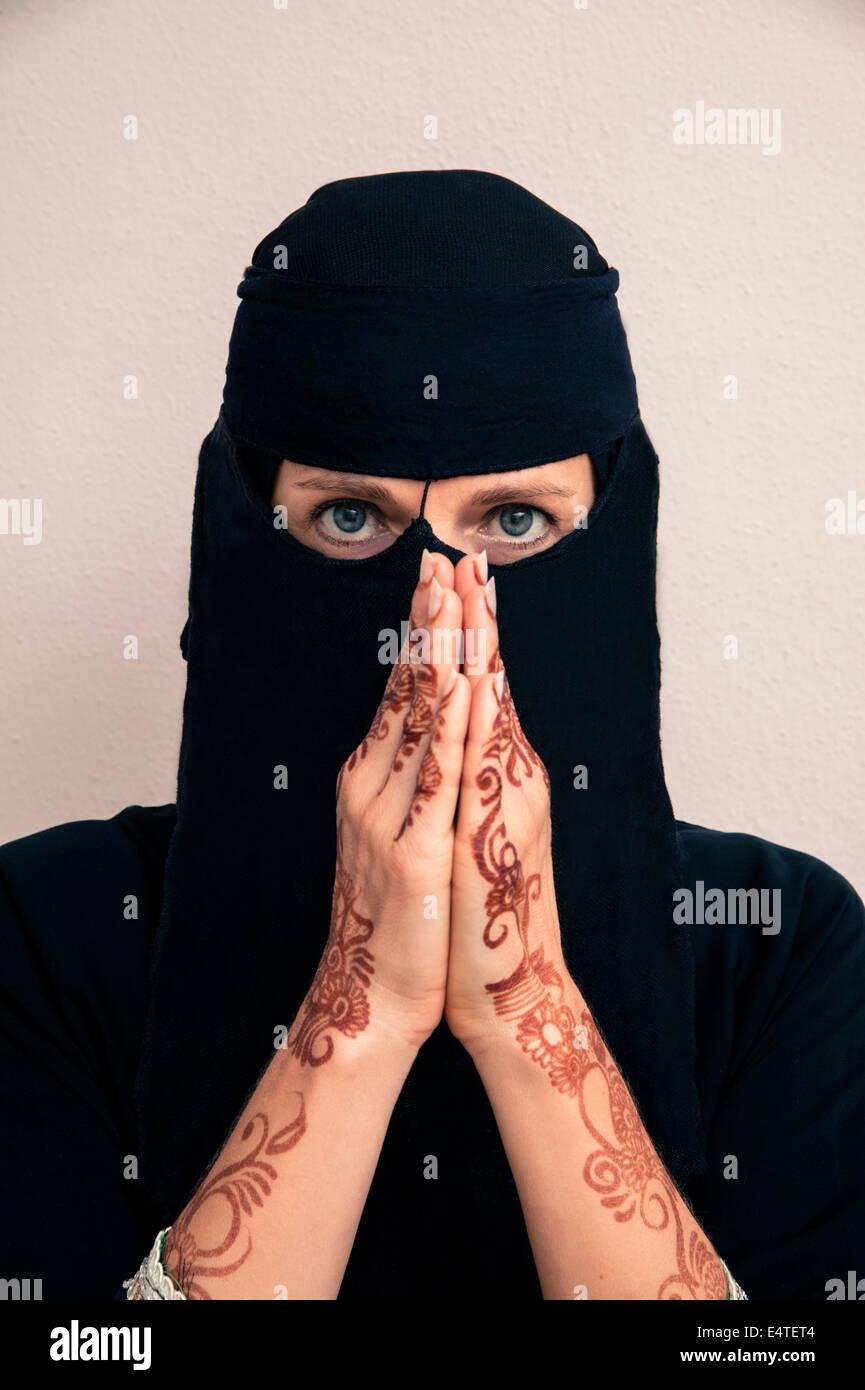 Porträt der Frau in schwarz Muslim Hijab und muslimische Kleidung, Hände, beten und mit Henna in arabischem Stil bemalt Stockfoto