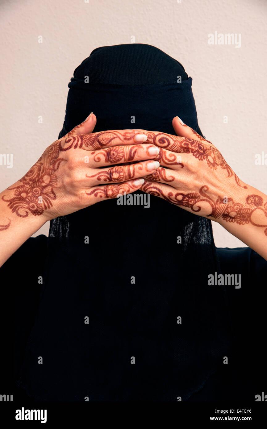 Porträt der Frau in schwarz Muslim Hijab und muslimische Kleidung, Hände, Augen bedecken und mit Henna in arabischem Stil bemalt Stockfoto