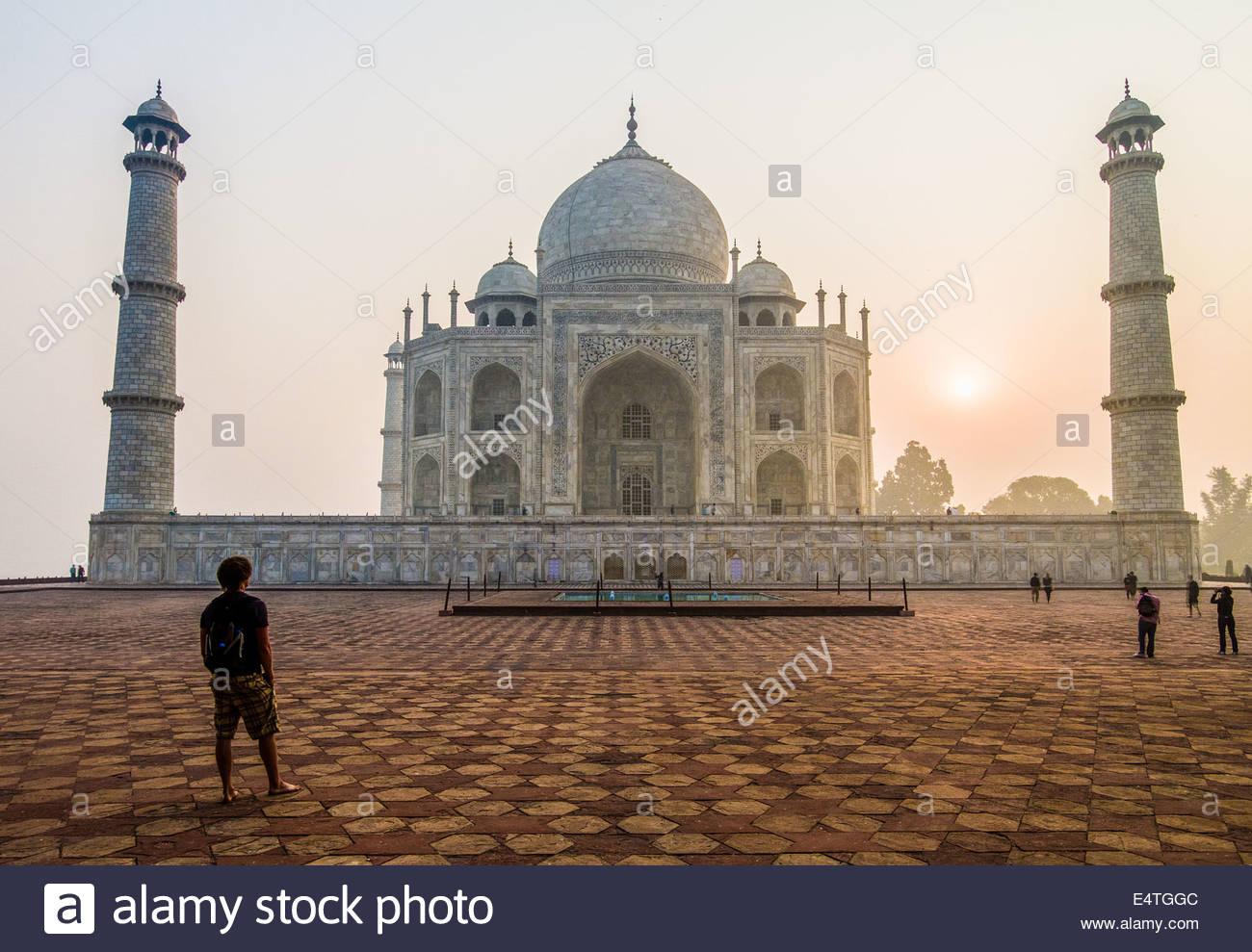 Ein Mann steht vor dem Taj Mahal, wie die Sonne hinter es, Agra, Indien, Asien aufgeht Stockbild