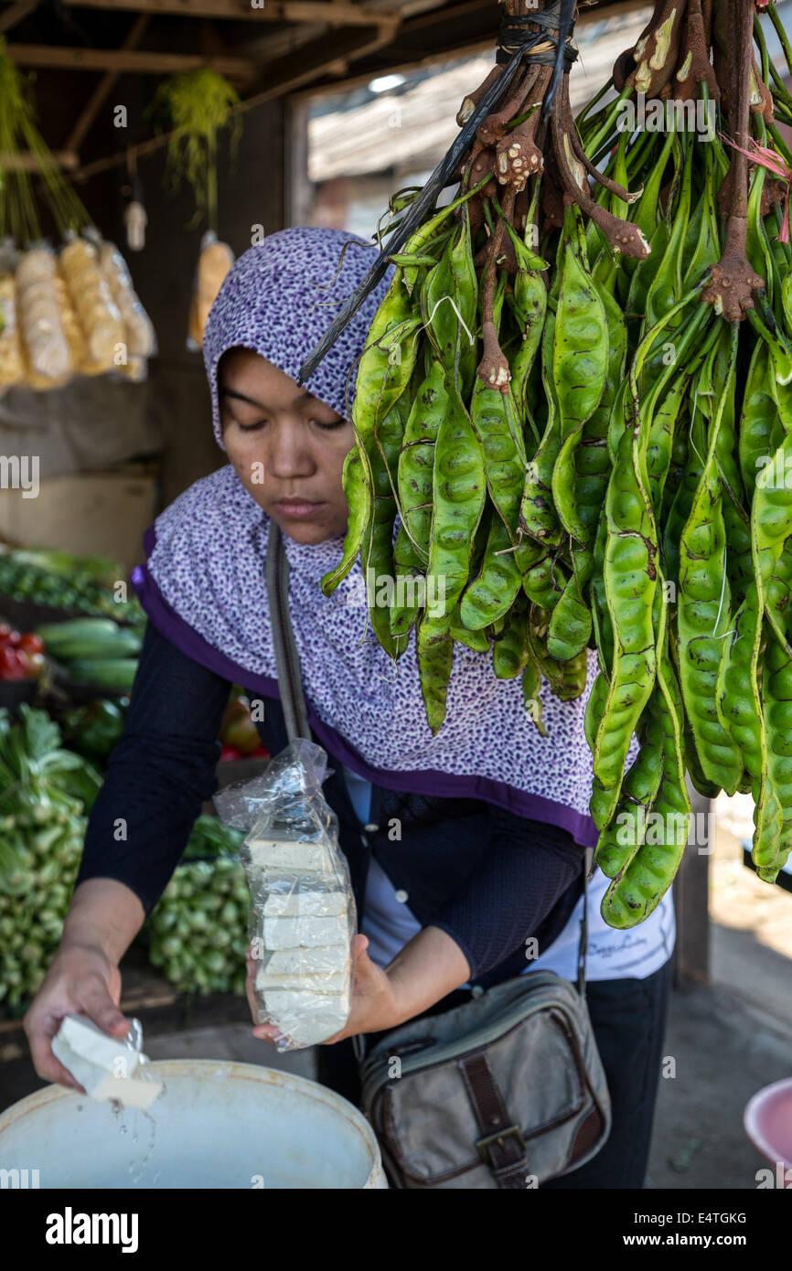 Jimbaran, Bali, Indonesien.  Frau kaufen Käse neben Petai, oder Pete, Bohnen, auch bekannt als bittere Bohne, Stockbild