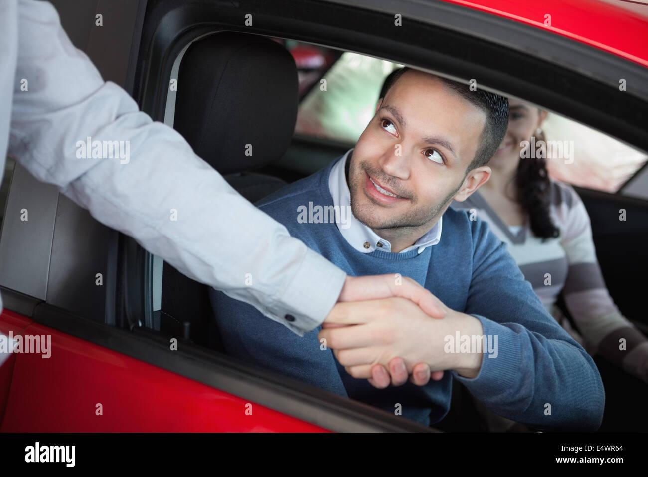 Man schüttelt die Hand von einem Autohändler Stockbild
