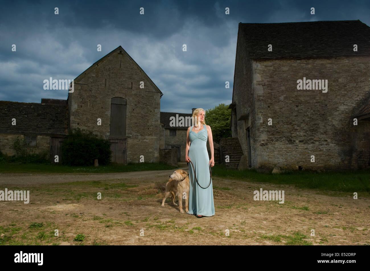 Eine Frau mit einem Lurcher Hund auf einem Hof unter Gewitterhimmel. Stockbild