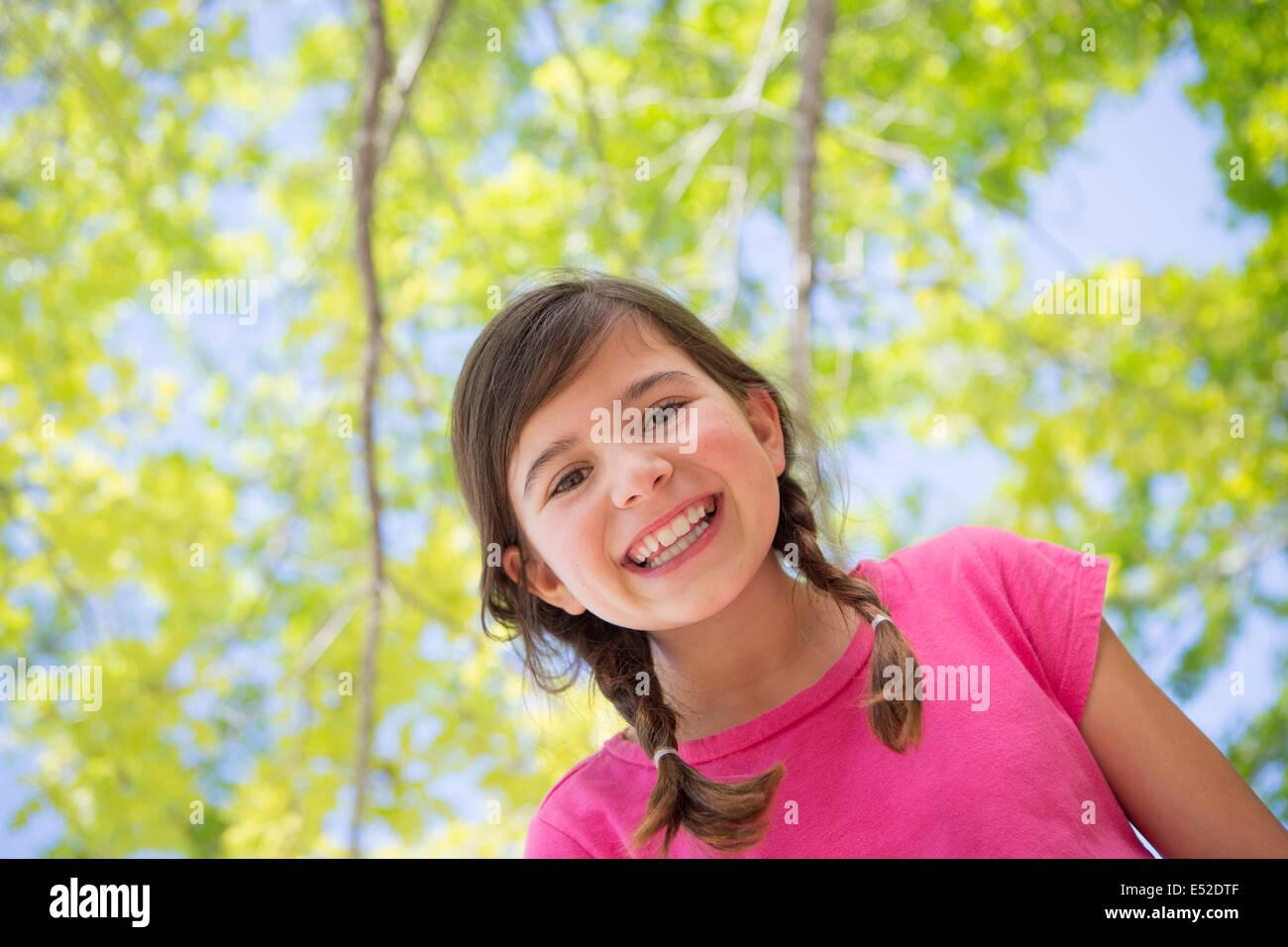 Ein junges Mädchen mit Zöpfen trägt ein pinkes Top unter einem Baldachin von Bäumen. Stockbild