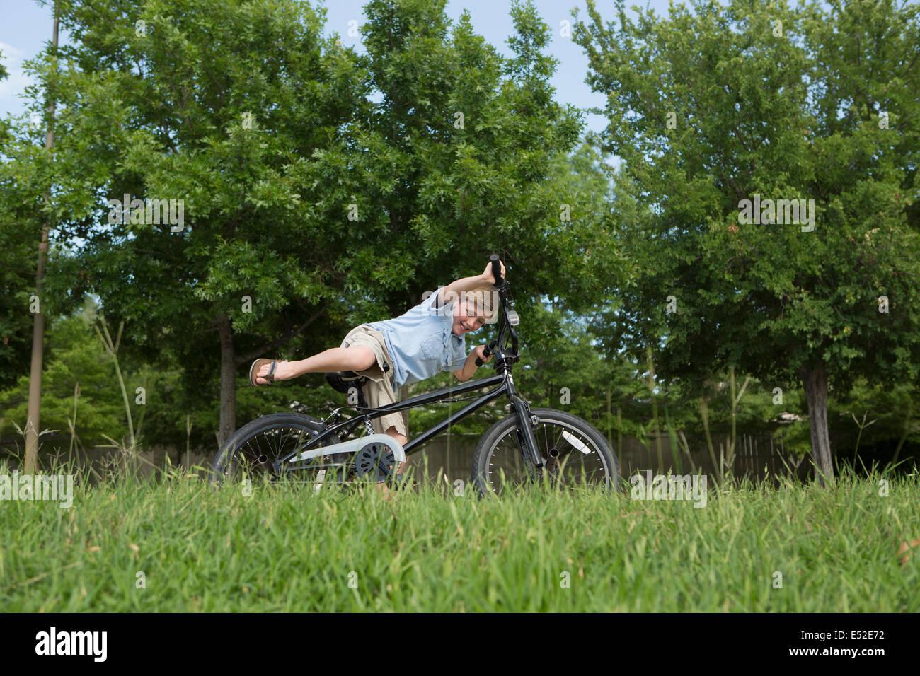 Ein kleiner Junge Sturz von seinem Fahrrad in einer Wiese overbalancing. Stockbild