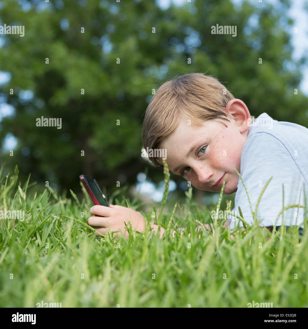 Ein kleiner Junge sitzt auf dem Rasen mit einer Hand gehalten elektronische Spiele Gerät. Stockbild