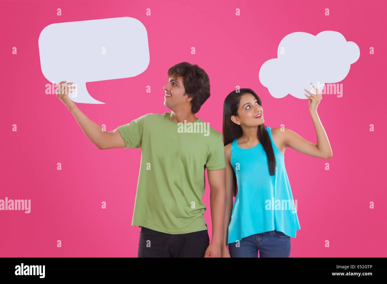 Nachdenklich junges Paar hält Kommunikation Bläschen vor rosa Hintergrund Stockfoto