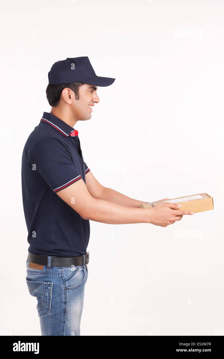 Profil-Schuss der Lieferbote so dass Paket vor weißem Hintergrund Stockbild