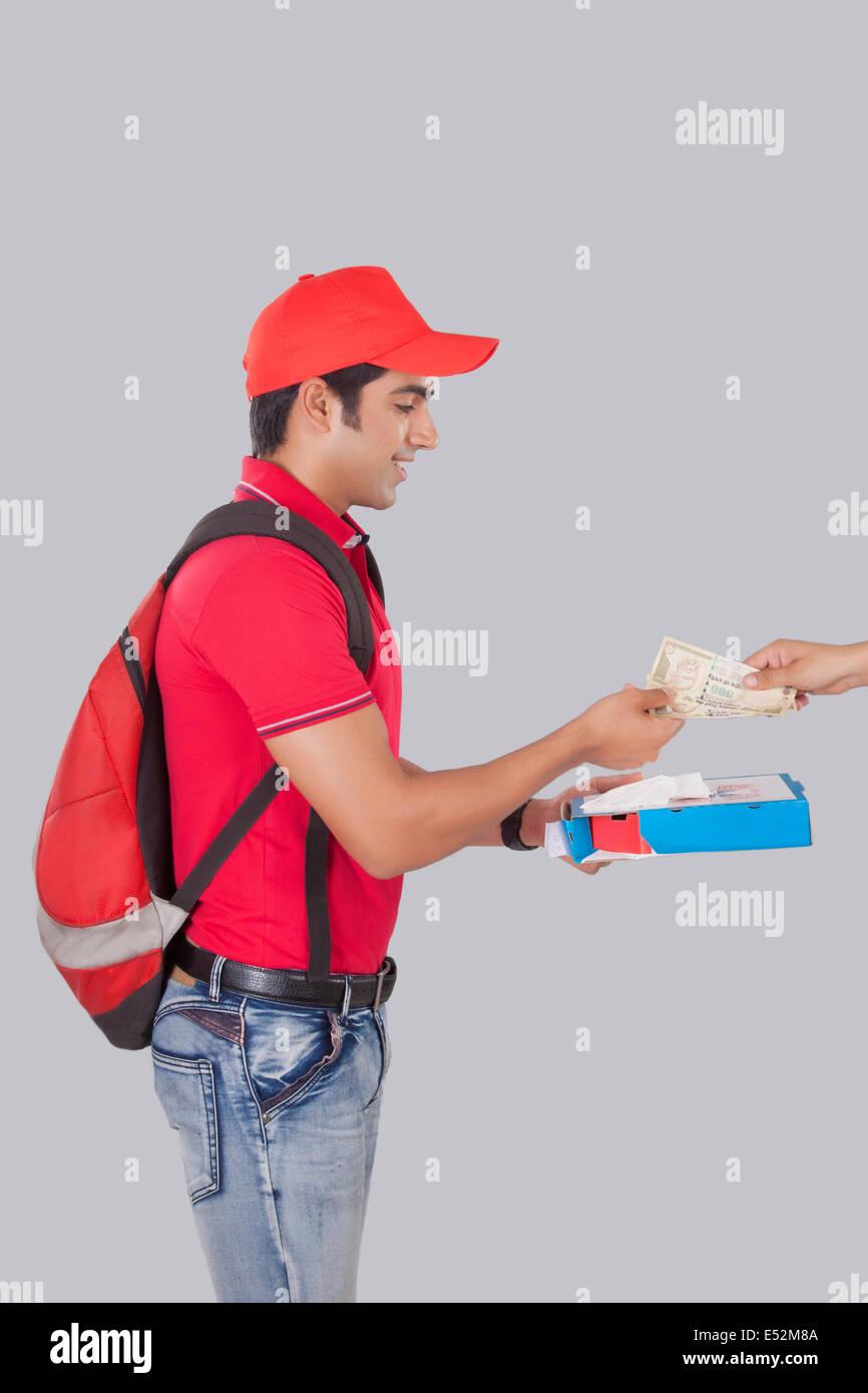 Profil-Schuss der Lieferbote liefern Pizza an Kunden über grauen Hintergrund Stockbild