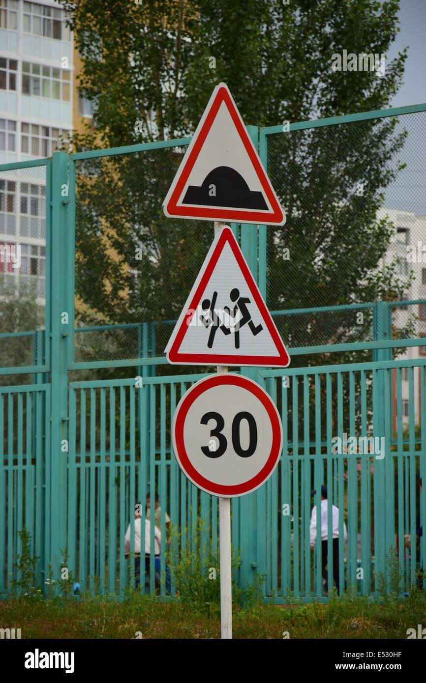 Drei Verkehrszeichen auf einem Pol: künstliches Hindernis, sorgfältig Kinder, Geschwindigkeitsbegrenzung Stockbild