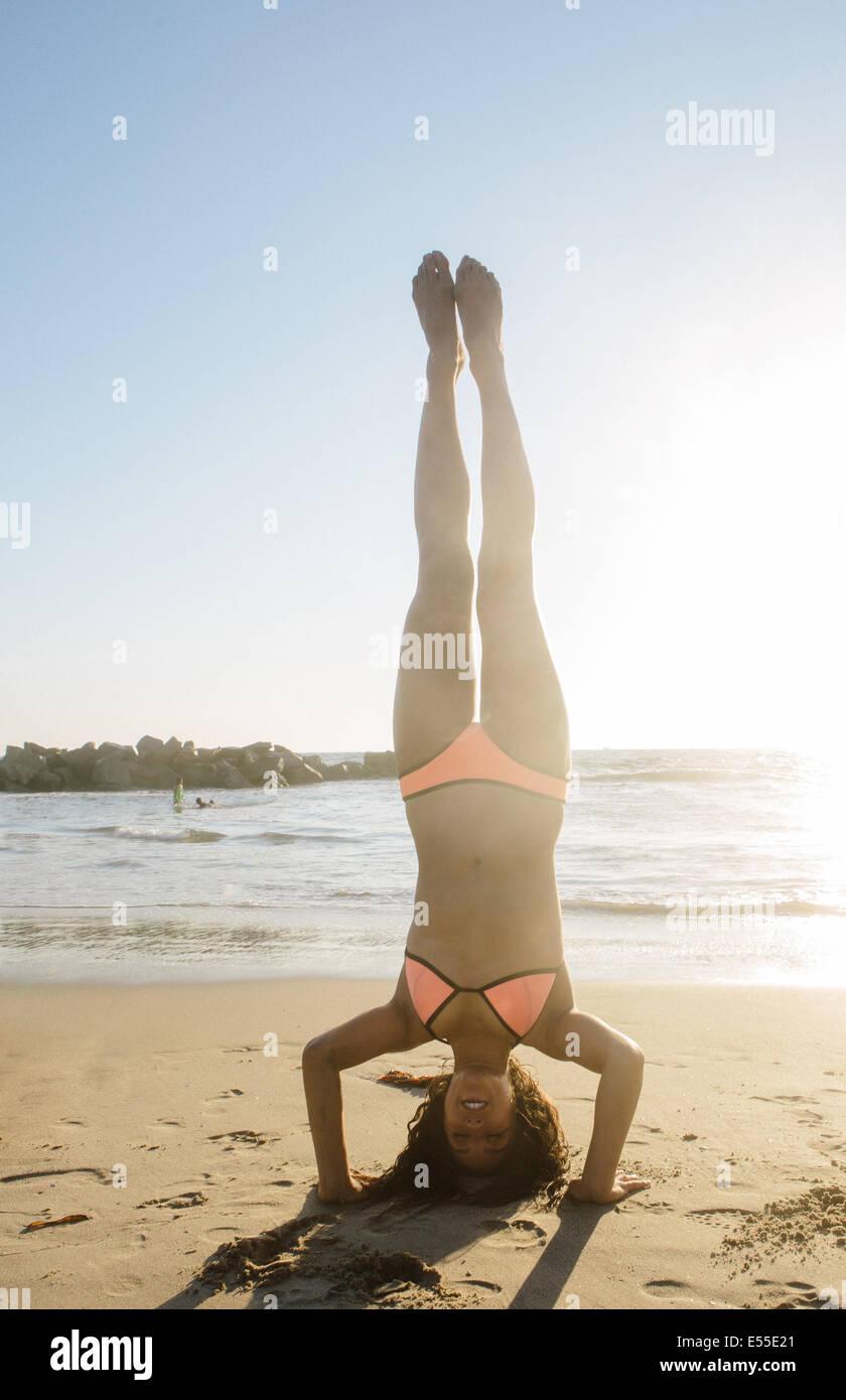 Fit junge Frau macht Kopfstand am Strand Stockbild