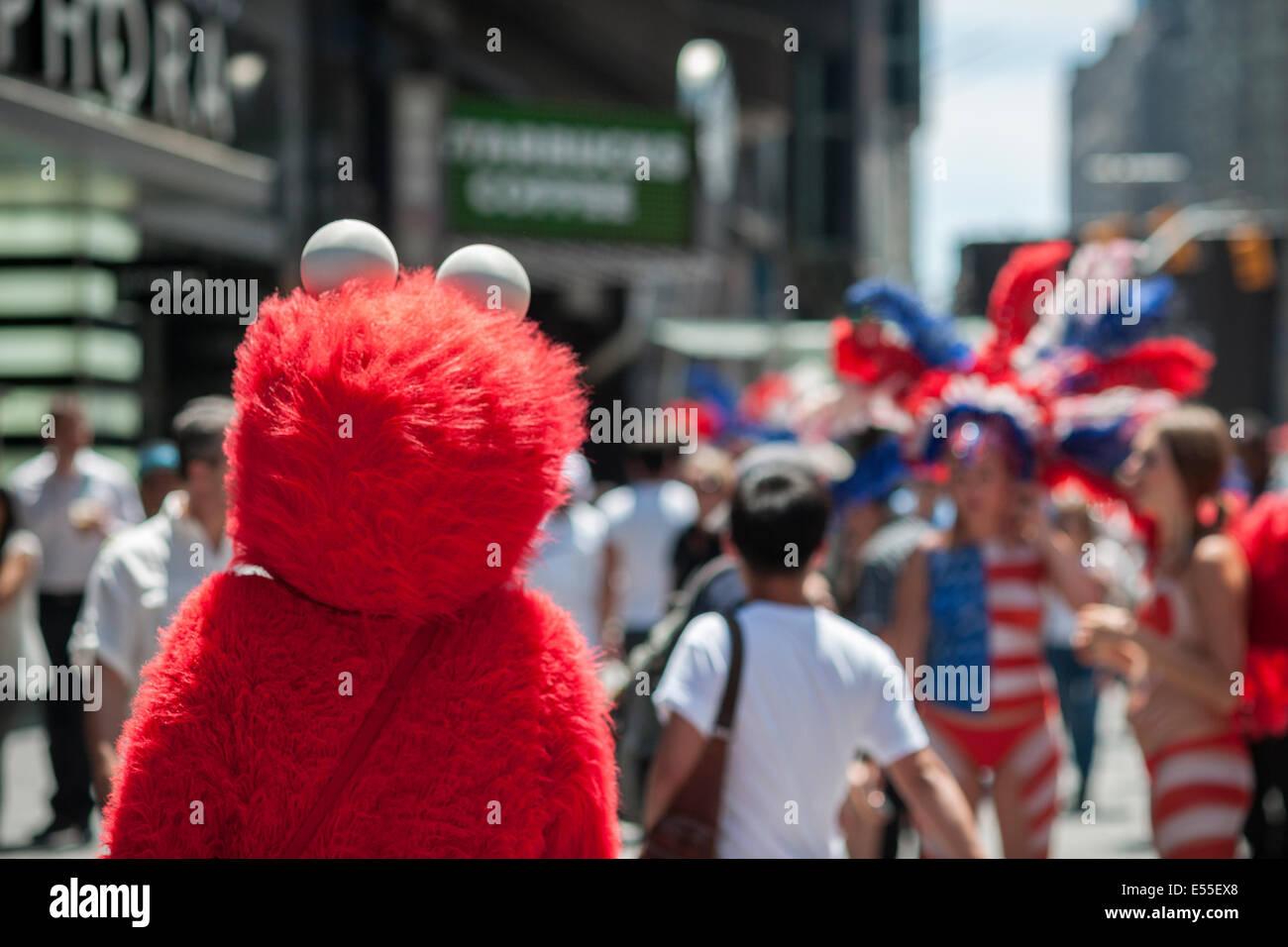 Elmo erbittet Touristen auf dem Times Square in New York auf Freitag, 18. Juli 2014. Stockbild