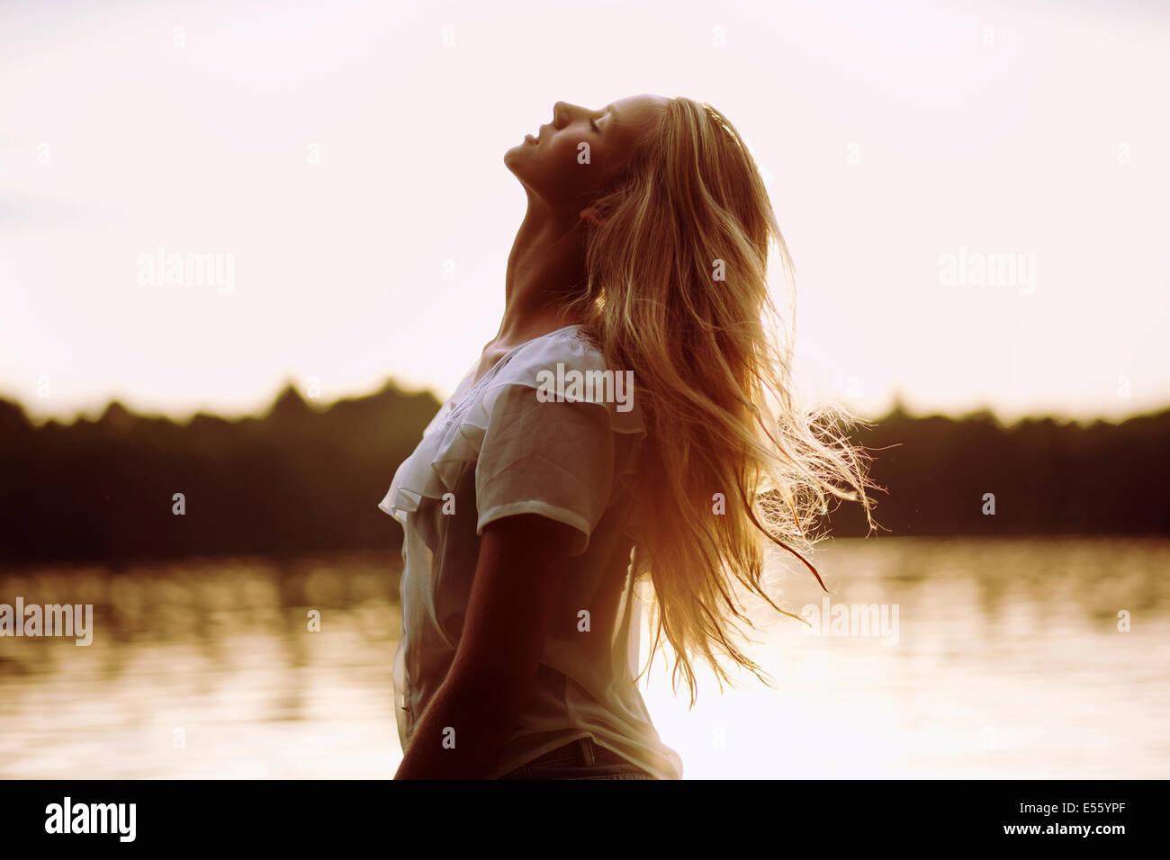 Porträt einer jungen Frau bei Gegenlicht Stockbild