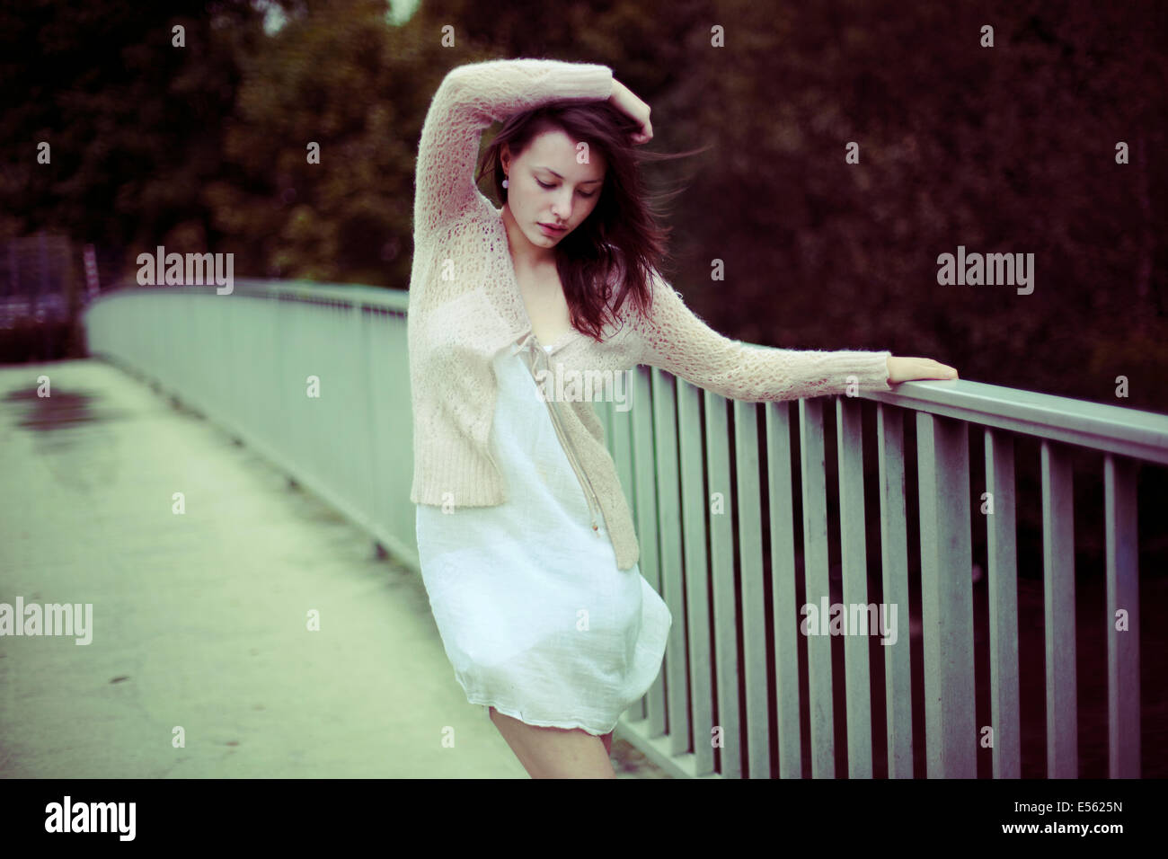 Junge Frau, die an das Geländer einer Brücke Stockbild