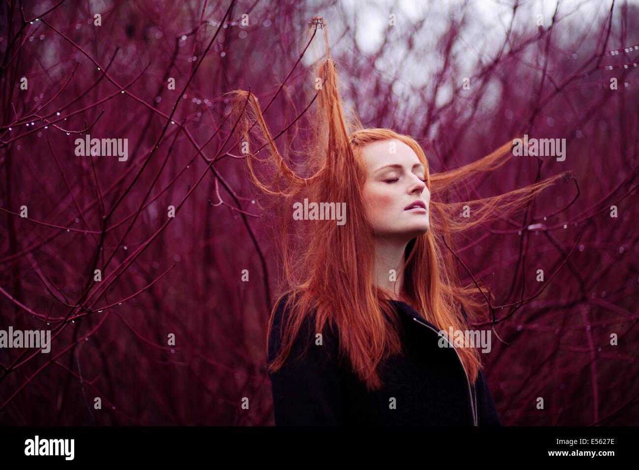 Frau mit langen roten Haaren zwischen Zweigen, Porträt Stockbild