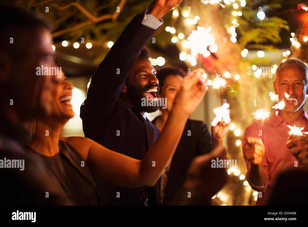 Freunde mit Wunderkerzen auf Party Spielen Stockbild