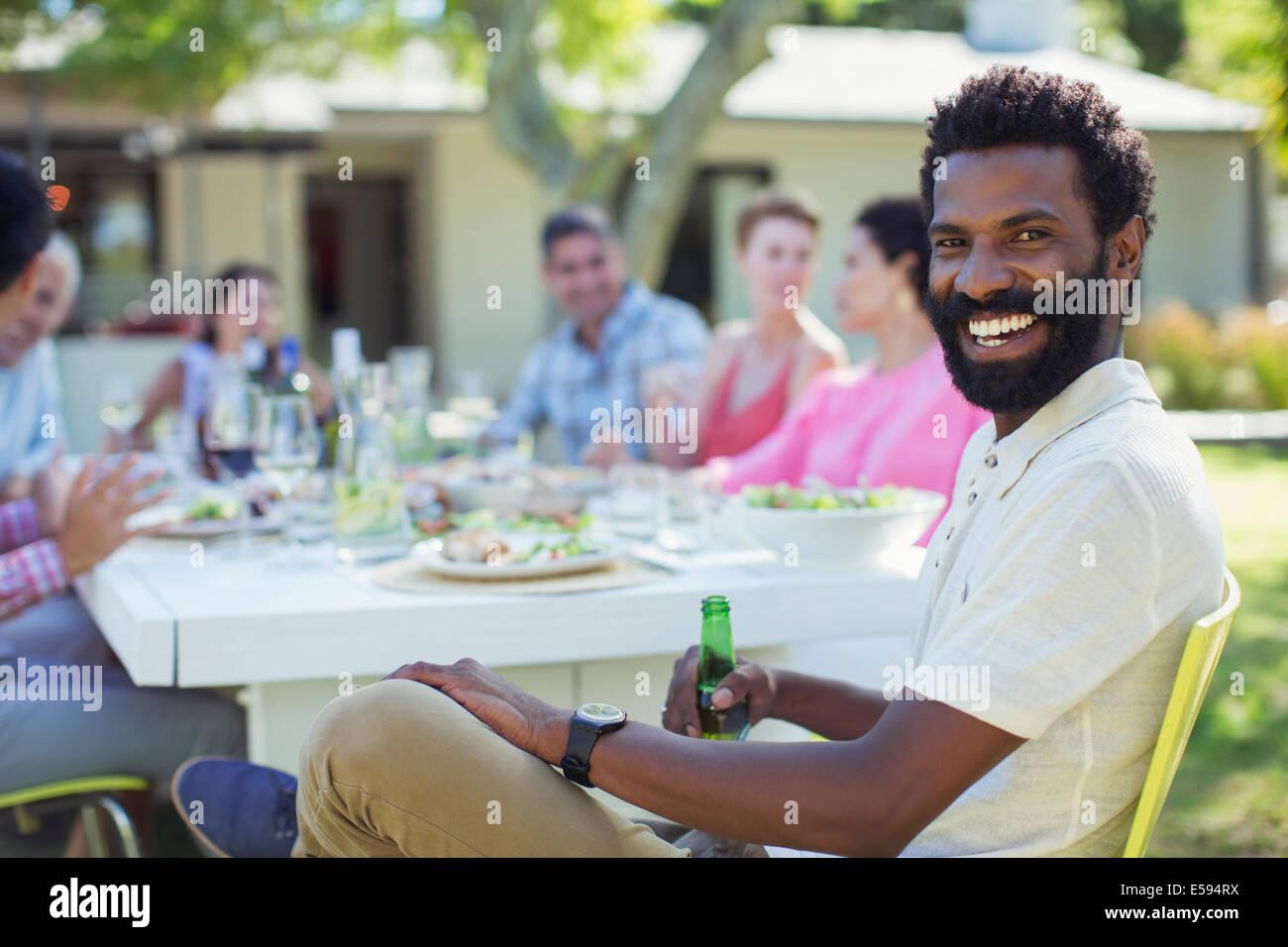 Mann lächelnd am Tisch im freien Stockbild