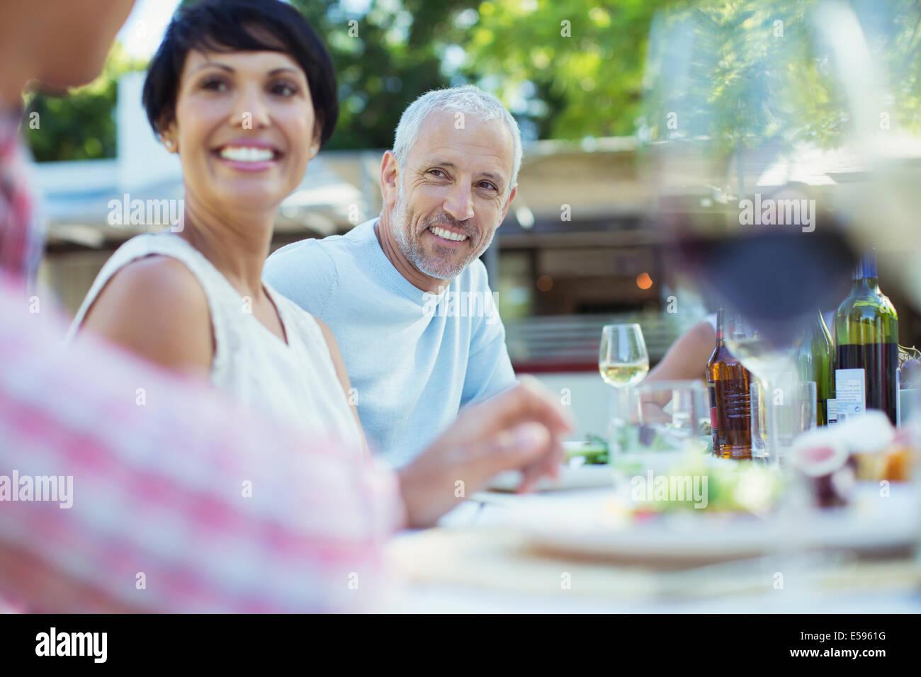 Paar lächelnd am Tisch im freien Stockbild