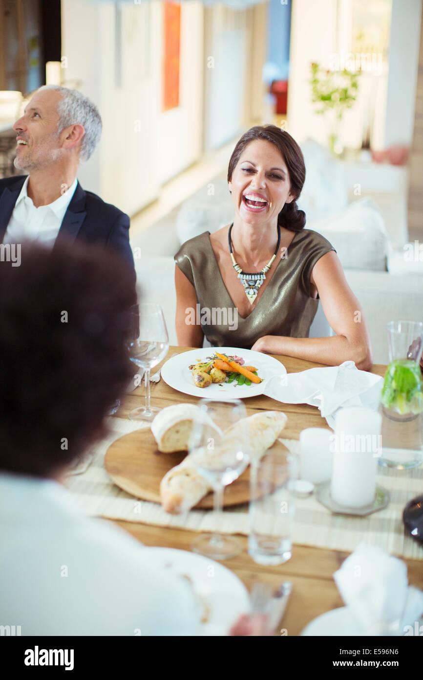 Bei Dinner-Party lachende Frau Stockbild
