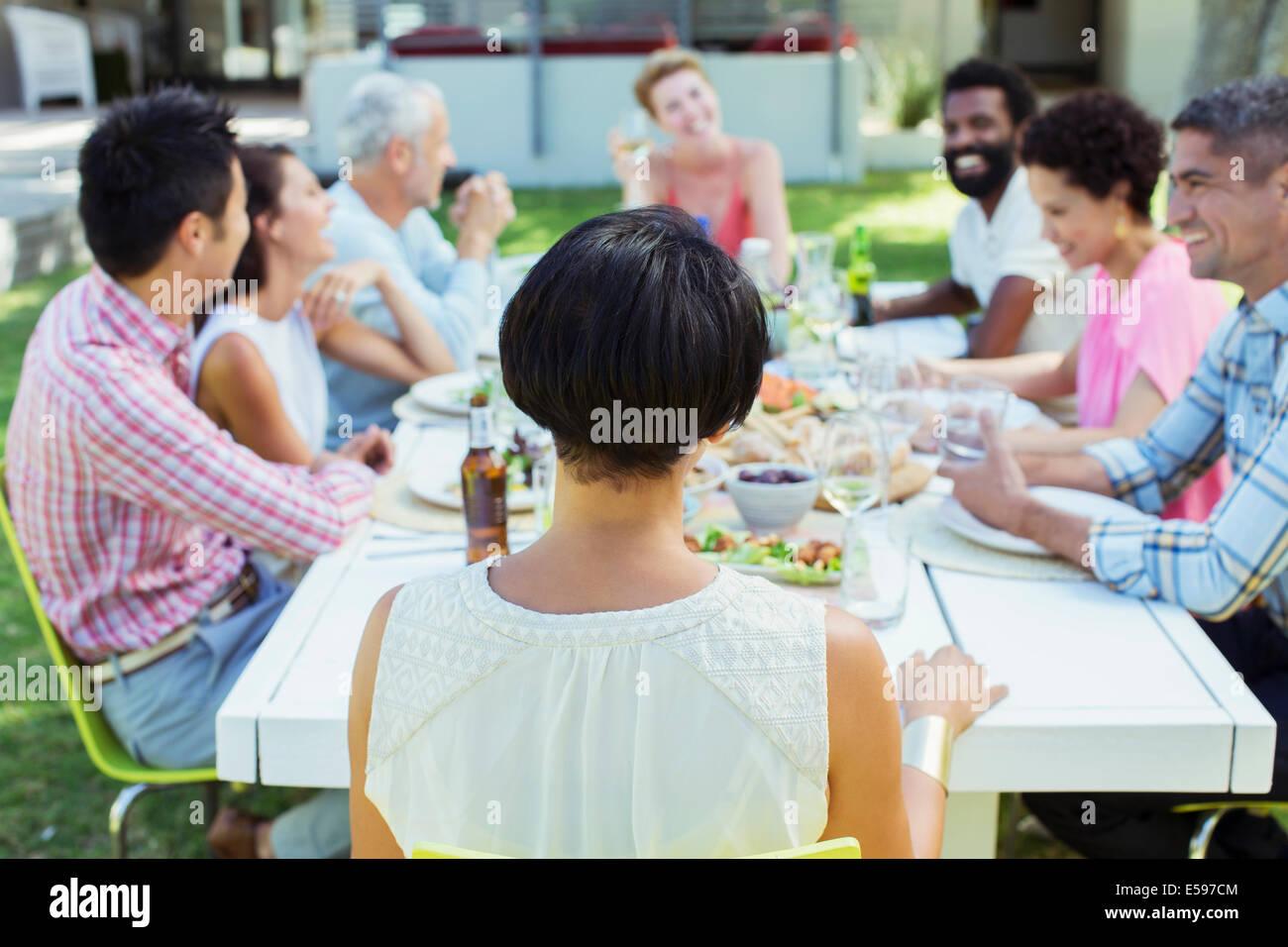 Freunde im Gespräch am Tisch im freien Stockbild
